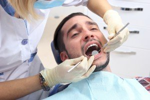 Man receives treatment procedure in the dental clinic.